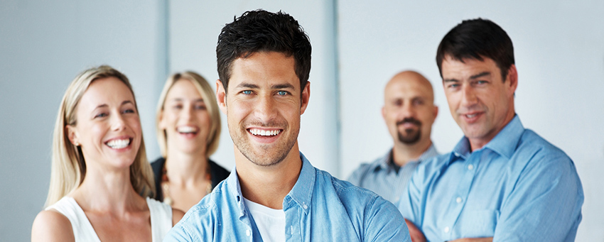 Portrait of a smart businessman standing with folded arms with his business team in background